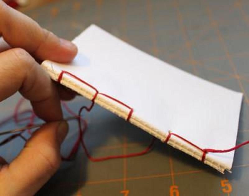Khâu các lớp giấy lại với nhau để cố định phần ruột sổ tay